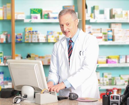 Portrait of an handsome senior pharmacist in his shop photo