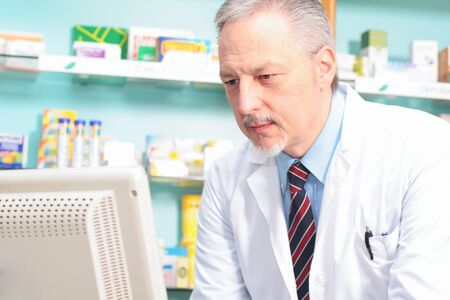 pharmacist: Portrait of a pharmacist using a computer