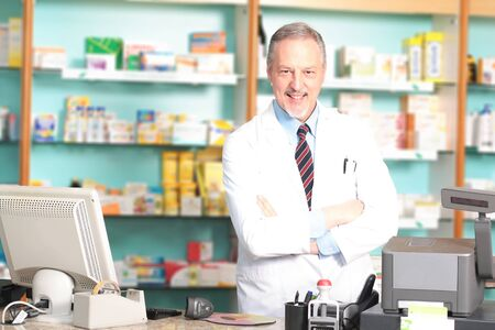 Portrait of an handsome pharmacist in his shop photo