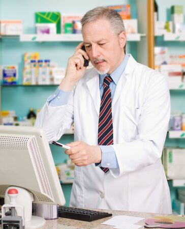 pharmacist: Portrait of an handsome senior pharmacist in his shop Stock Photo