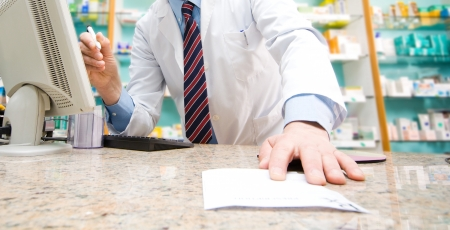 Pharmacist taking a prescription from a customer photo