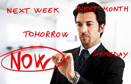 excuse: Businessman writing big now word surrounded by procrastination excuses Stock Photo