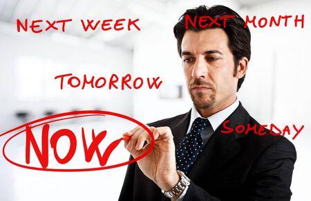 procrastination: Businessman writing big now word surrounded by procrastination excuses Stock Photo