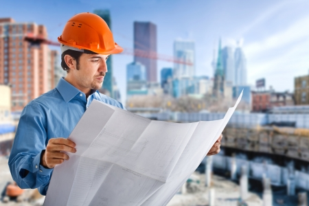 Portrait of a site manager reading a blueprint photo
