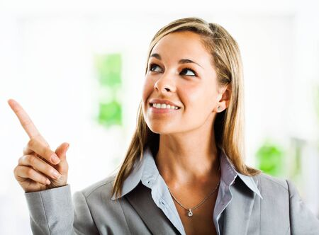 Portrait of a young businesswoman pointing her finger up photo