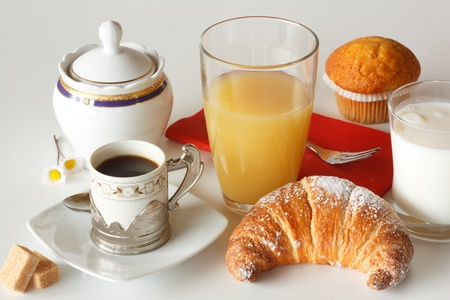 Continental breakfast with coffee, milk, orange juice and croissants served on a table Stock Photo - 14020374