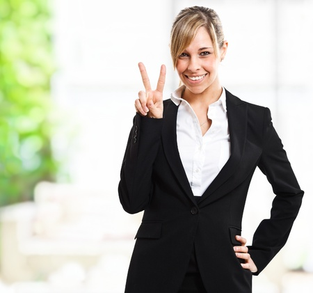 Smiling woman doing victory sign Stock Photo - 14013054