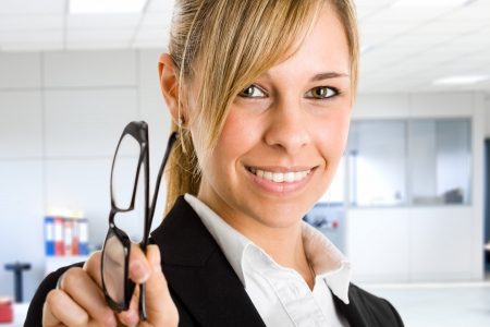 Portrait of a beautiful smiling businesswoman holding her eyeglasses photo