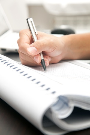 Businessman writing on a document photo