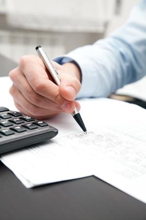 Business man using a calculator photo