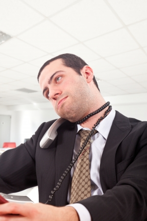 Young man strangling himself with a telephone cord in an office environment photo