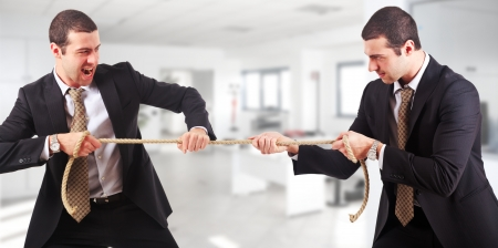 Businessmen twins pulling a rope in an office environment photo