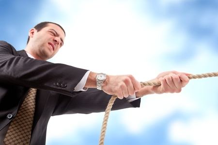 Angry businessman pulling a rope  Blue sky with clouds in the background  photo