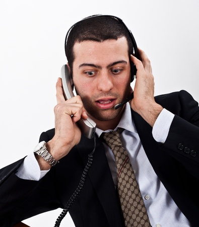 hard sell: Portrait of a stressed businessman using telephone and headphones at the same time