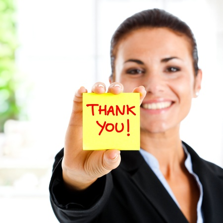 grateful: Happy businesswoman showing greetings on a post-it Stock Photo