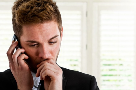 troublesome: Worried businessman using a cell phone