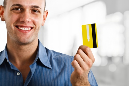 Portrait of a young happy man showing a credit card photo