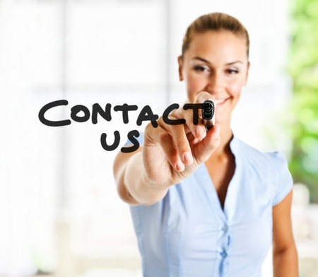 contact us: Beautiful woman writing Contact us on the screen