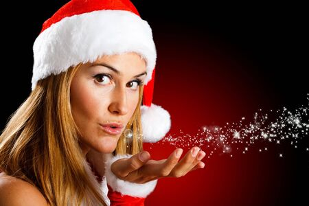 Portrait of a beautiful Christmas girl blowing stars photo