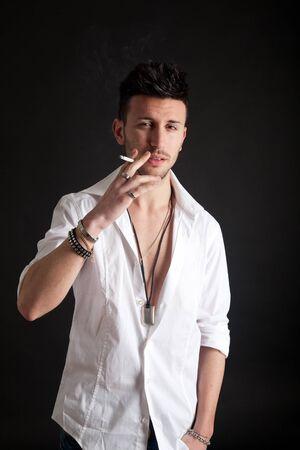 joven fumando: Moda retrato de un hombre joven y guapo