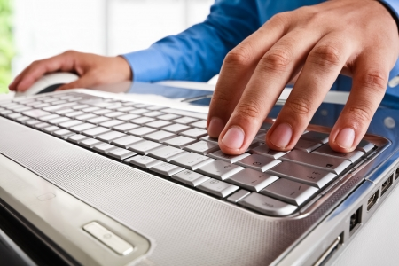 Close-up of a worker using a laptop computer photo