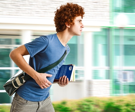 running late: Portrait of a young man running to school