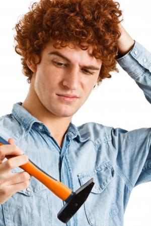 clumsy: Retrato de un hombre torpe tratando de usar un martillo Foto de archivo