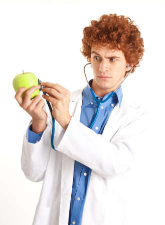 Portrait of a funny doctor examining an apple Stock Photo - 14168983