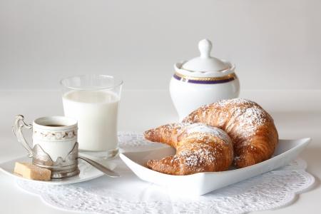 Desayuno continental con café, leche y medialunas que se presentan en una tabla