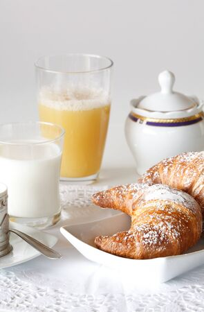Continental breakfast with coffee, milk, orange juice and croissants served on a table Stock Photo - 14169068