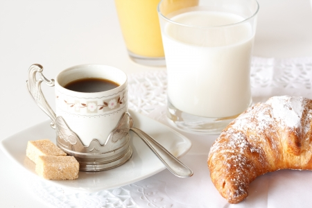 Continental breakfast with coffee, milk, orange juice and croissants served on a table Stock Photo - 14169074