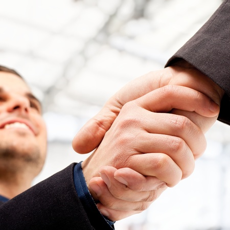 satisfied people: Business people shaking hands  Bright blurred background  Stock Photo