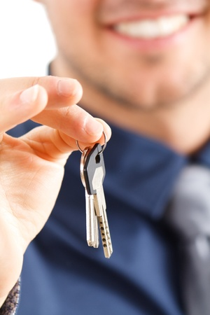 Smiling businessman giving keys to you  photo