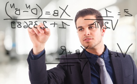Young businessman writing math formulas on the screen. photo