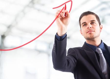 contabilidad: Empresario dibujar una flecha ascendente, lo que representa el crecimiento del negocio.