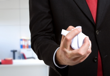 compromising: Businessman crumpling a document in his office
