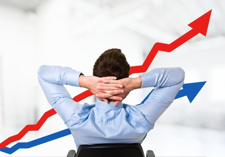 gains: Relaxed man looking at the growth of his business Stock Photo