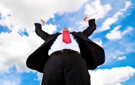 Portrait of a businessman raising arms photo