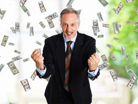 earn: Feliz el hombre disfruta de una lluvia de dinero