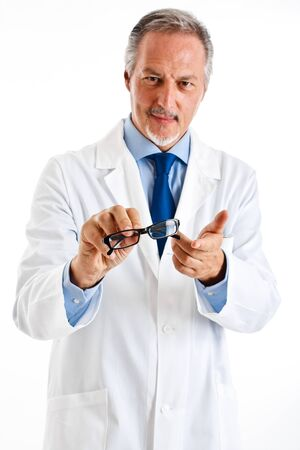 Portrait of a friendly doctor smiling giving a pair of eyeglasses Stock Photo - 14329996