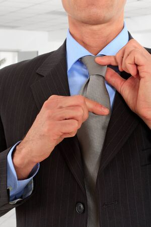conceited: Sophisticated businessman adjusting his tie in an office environment
