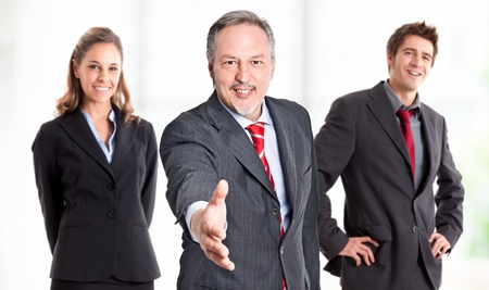 Friendly businessman giving his hand to seal a deal Stock Photo