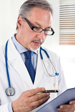 Handsome senior doctor reading a case history Stock Photo - 14330113