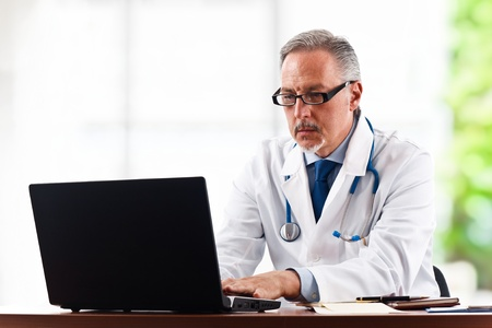 Portrait of a mature doctor using his laptop computer photo