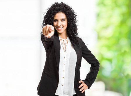 Portrait of a smiling beautiful woman pointing her finger at you photo