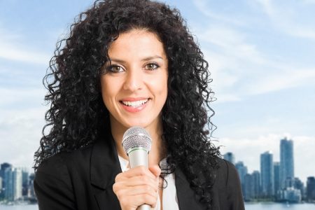 newsreader: Portrait of a woman speaking in a microphone