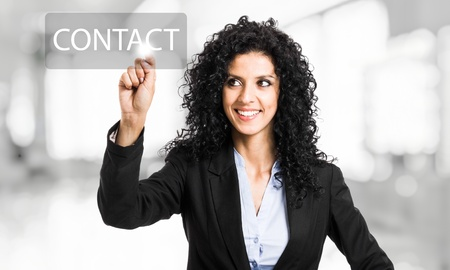 email contact: Beautiful businesswoman touching a contact button on the screen Stock Photo