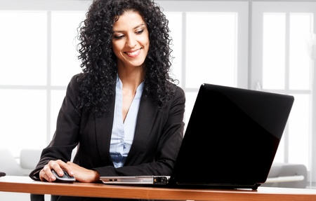 Portrait of a young smiling businesswoman using her computer photo