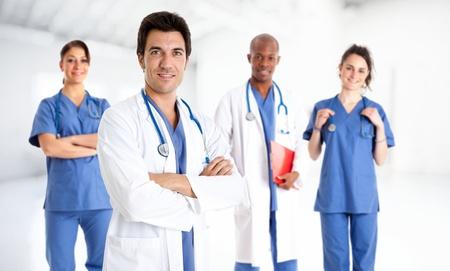 Portret van een glimlachende dokter in de voorkant van zijn team
