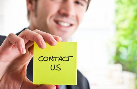Man showing a post-it with contact Stock Photo - 14375470